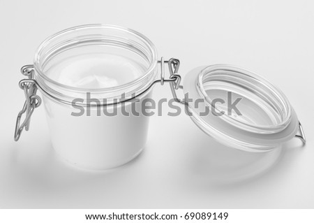 Opened glass jar of cosmetic cream on light background.