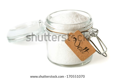 Opened glass jar with salt. Isolated on white. - stock photo