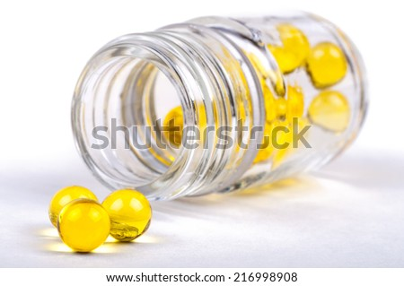 Opened glass jar with yellow capsules of fish oil lying on white table. Close-up with shallow DOF. Isolate on white background. - stock photo