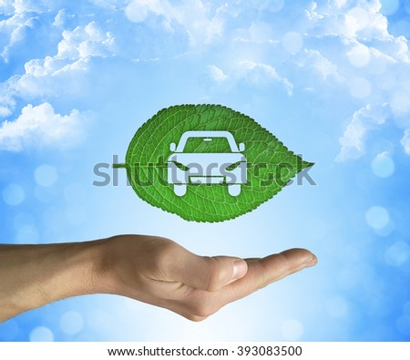 Opened hand holding a green leaf with a car icon inside on a blue sky background. Eco car concept - stock photo