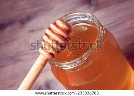 opened honey jar on wood table with honey wooden dipper on top
