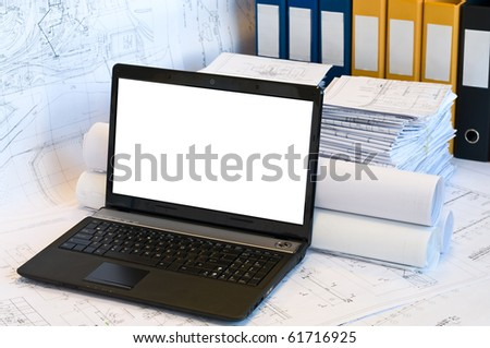 Opened laptop and stack of project drawings. Rolled papers. Working place. White screen - stock photo