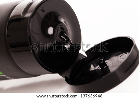 Opened lotion tube with black cap on a white table - stock photo