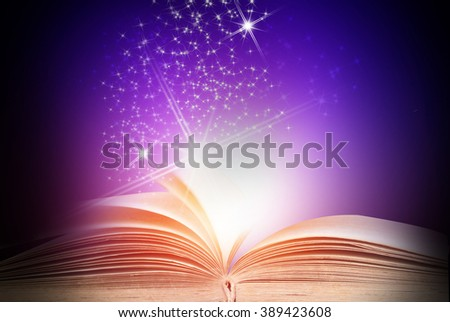Opened magic book on abstract blue background  - stock photo