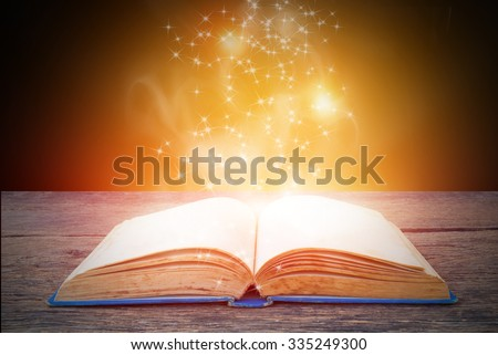 Opened magic book on abstract gold background