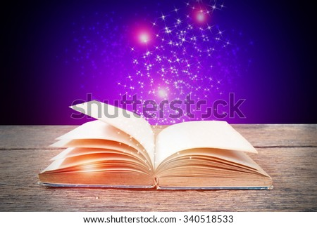 Opened magic book on abstract pink blue background