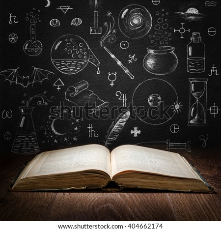 Opened magic book with alchemy symbols on chalkboard. Philosophy, spirituality, occultism, chemistry, science, alchemy and magic symbols. - stock photo