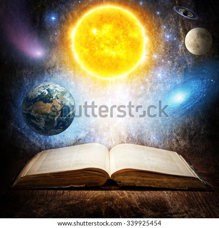 Opened magic book with sun, earth, moon, saturn, stars and galaxy. Concept on the topic of astronomy or fantasy.  Elements of this image furnished by NASA. - stock photo