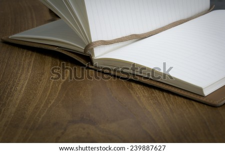 Opened note book on wooden table