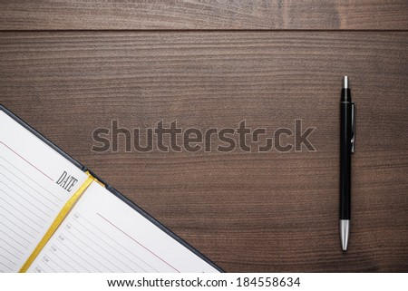 opened notebook and pen on the wooden table - stock photo