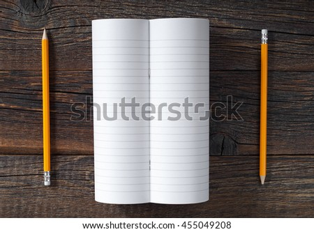 Opened notebook and pencil on dark wooden background, top view