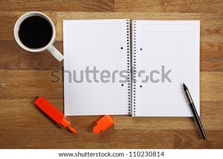 Opened notebook, cup of coffee and pen on wooden office desk. - stock photo