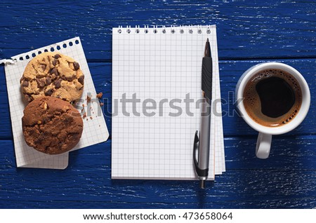 Opened notebook, cup of hot coffee and cookies on a dark blue background, top view