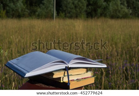 Opened notebook is on the stack of books in the field
