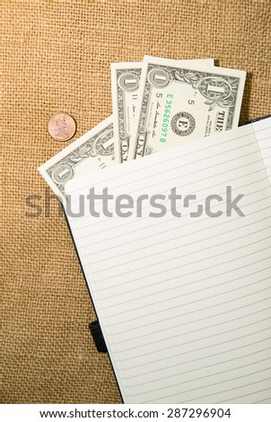 Opened notebook with a blank sheet and money on the old tissue - stock photo