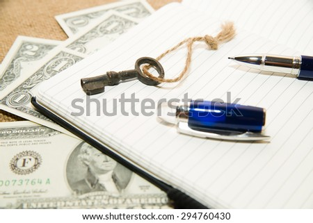 Opened notebook with a blank sheet, pen, key and money on the old tissue - stock photo
