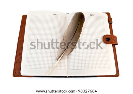 Opened notebook with a brown bird feather isolated on white background - stock photo