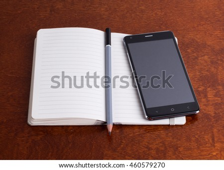 Opened notebook with a pencil and a smartphone, brown surface