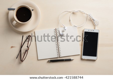 Opened notebook with blank area, pen, smart phone, in ear headset, and coffee cup on wood table in morning time - stock photo