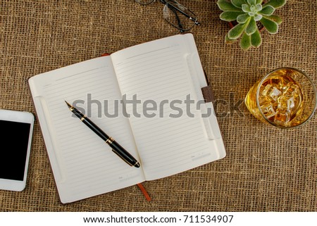Opened notebook with blank area, pen, smartphone, and coffee cup on table in morning time