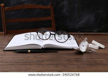 Opened notebook with eyeglasses and clock on wooden table