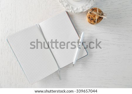 Opened notebook with pile of cookies on white wooden table