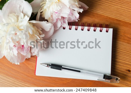 opened notebook with the pen,  copy space and flowers - stock photo