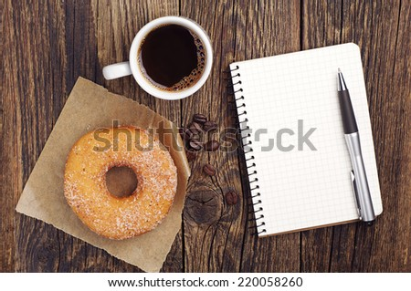 Opened notepad and cup of coffee with donut on old wooden table. Top view - stock photo