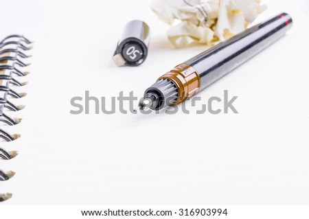 Opened notepad, pen and crumpled paper on white background