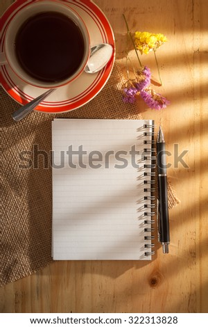 Opened notepad with blank area for text or message, pen, and a cup of hot tea on wood table in cafe with light effect from window in morning