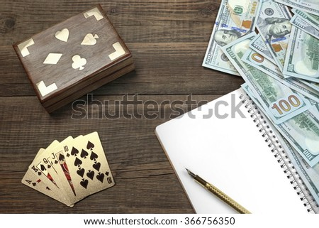 Opened Notepad With Blank White Page, Fountain Pen, Dollar Cash And Two Unopened Playing Cards Deck In Box On Wood Table Background With Space, Top View - stock photo