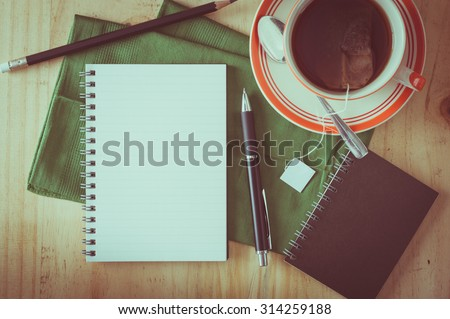 Opened notepad with pen and a cup of hot tea on wood table in cafe with film filter effect - stock photo