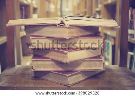 Opened old book in library room, education concept,vintage tone - stock photo