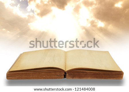 Opened old book with beautiful sky background - stock photo