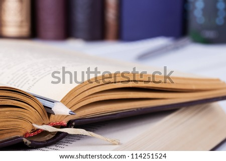 Opened old book with grey pencil and several books on the background - stock photo