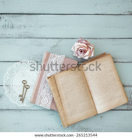 Opened old book with lace, rose and keys on shabby chic mint background, top view point - stock photo