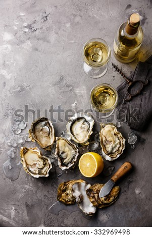 Opened Oysters Fines de Claire and white wine on gray concrete texture background - stock photo