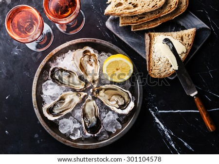 Opened Oysters on metal plate, bread with butter and rose wine on dark marble background  - stock photo