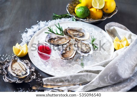 Opened Oysters Speciale de Claire in ice on a plate with sauce. Restaurant food over wooden table