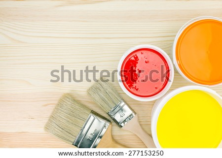 opened paint cans with brushes on wooden background - stock photo
