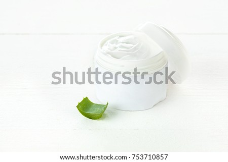 Opened plastic container with cream and aloe on a white table background.