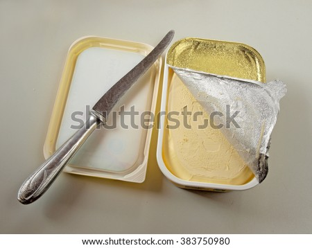 Opened plastic margarine box with half removed foil and table knife.