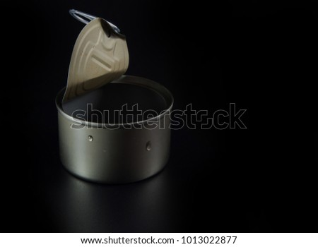 Opened pull cap of empty food can on black background