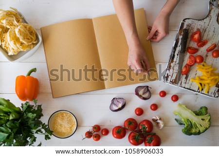 Opened recipe book hands woman front stock photo royalty free opened recipe book in the hands of woman in front of a table with utensils and forumfinder Gallery