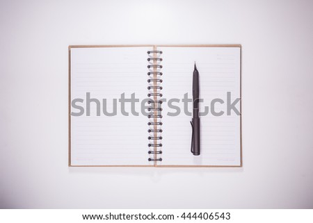 opened recycled paper notebook ,black calligraphic pen and white rubber in white desktop with vignette effect