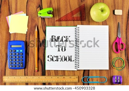 Opened school notebook with arrangement of school supplies and Back to School text over a wooden desk background - stock photo