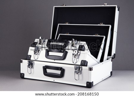 Opened silvery suitcases on grey background