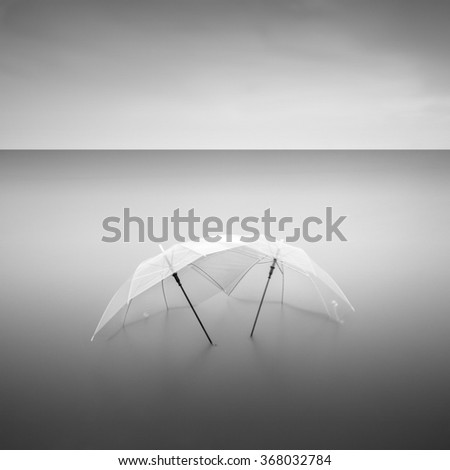 Opened two transparent umbrella on sea background with long exposure black and white fine art - stock photo