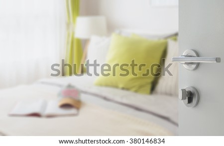 opened white door to modern bedroom with green pillow on bed
