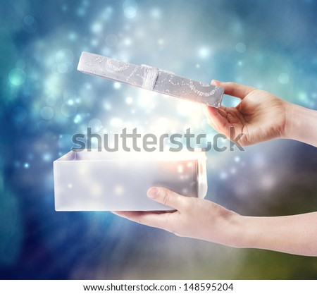 Opening a gift box with magical special effects lights - stock photo